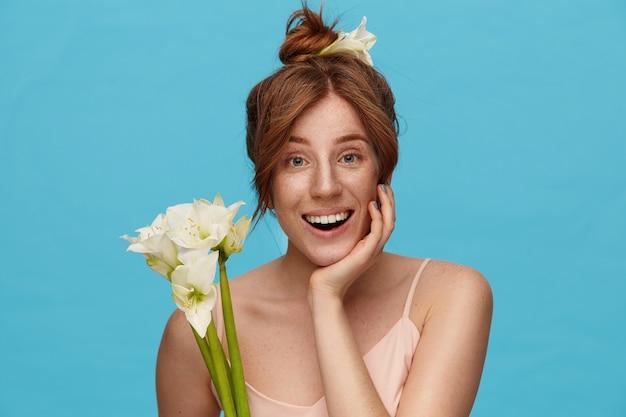 白い花で青い背景の上にポーズをとって、彼女の顔の下で手を上げたままで、カメラで幸せそうに笑っている間、結び目で彼女のセクシーな髪を着ているうれしそうな若い素敵な女性
