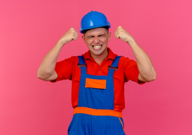 Joyful young male builder wearing uniform and safety helmet showing yes gesture