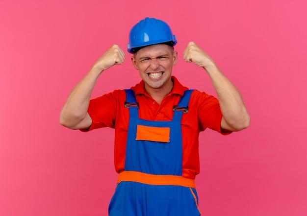 Giovane costruttore maschio allegro che indossa l'uniforme e il casco di sicurezza che mostra il gesto di sì