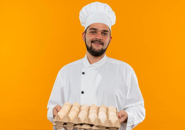 Joyful young male cook in chef uniform holding carton of eggs looking  isolated on orange wall