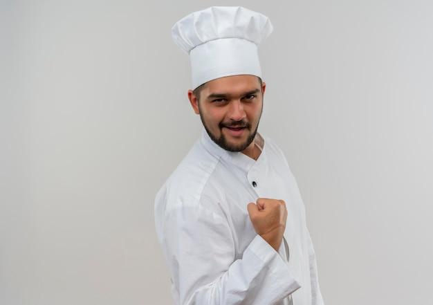 コピー スペースで白い壁に分離された拳を握り締めるシェフの制服を着たうれしそうな若い男性料理人