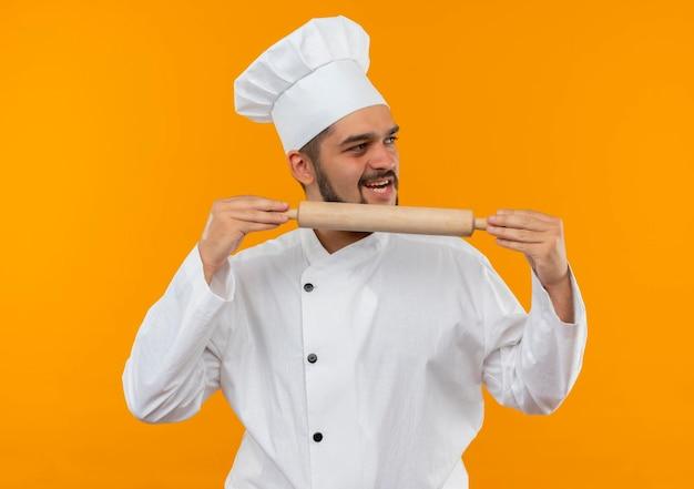 麺棒を持ち、オレンジ色の壁に隔離された側を見るシェフの制服を着たうれしそうな若い男性料理人