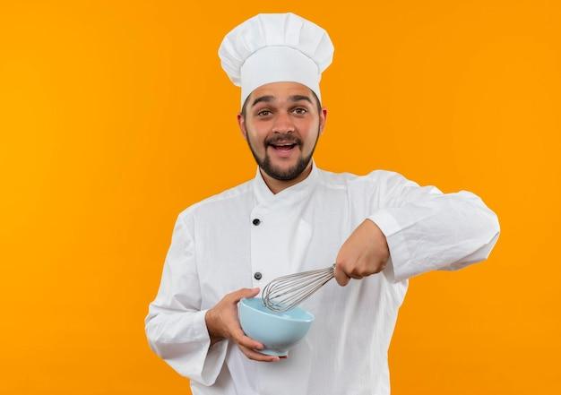 コピー スペースでオレンジ色の壁に分離された泡立て器とボウルを保持しているシェフの制服を着たうれしそうな若い男性料理人