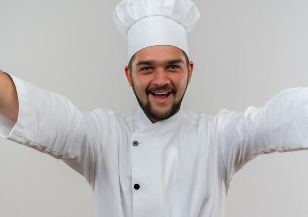 흰 벽에 고립 된 두 팔을 벌려 찾고 요리사 유니폼에 즐거운 젊은 남성 요리사