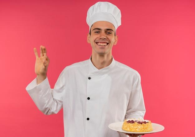 Радостный молодой мужчина-повар в униформе шеф-повара держит торт на тарелке и показывает жест на изолированной розовой стене