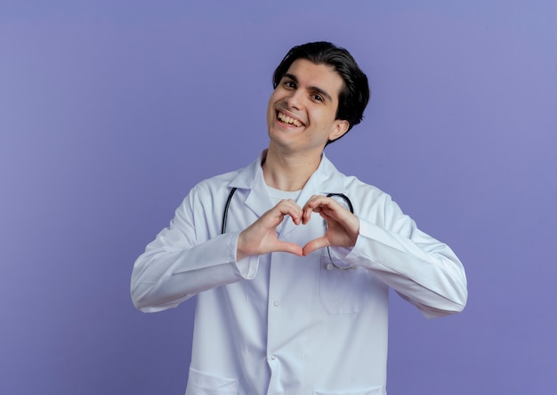Joyful young male doctor wearing medical robe and stethoscope  doing heart sign isolated on purple wall with copy space