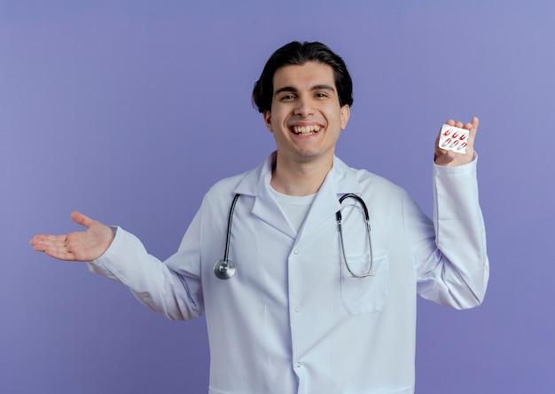 Gioioso giovane medico maschio che indossa abito medico e stetoscopio che mostra confezione di capsule mediche e mano vuota isolata sulla parete viola