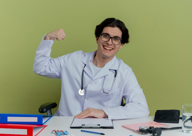 Joyful young male doctor wearing medical robe and stethoscope with glasses sitting at desk with medical tools  doing strong gesture isolated on olive green wall