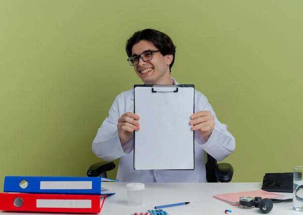 Gioioso giovane medico maschio che indossa abito medico e stetoscopio con gli occhiali seduto alla scrivania con strumenti medici guardando mostrando appunti isolati