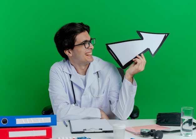 Joyful young male doctor wearing medical robe and stethoscope with glasses sitting at desk with medical tools turning head to side holding arrow mark pointing at side isolated on green wall