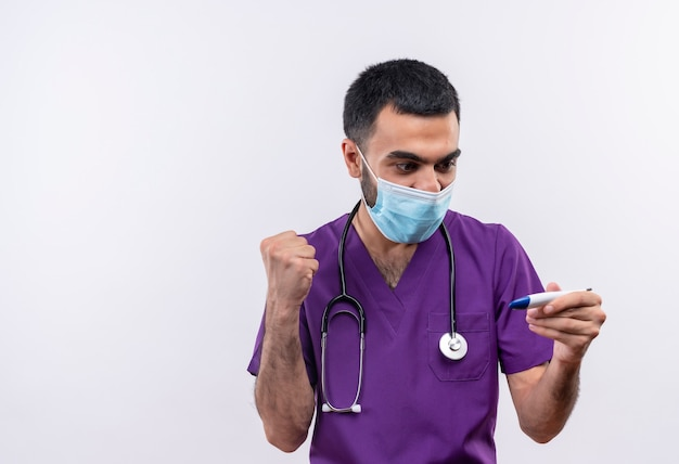 Gioioso giovane medico maschio che indossa abbigliamento chirurgo viola e maschera medica stetoscopio guardando il termometro in mano che mostra sì gesto sul muro bianco isolato