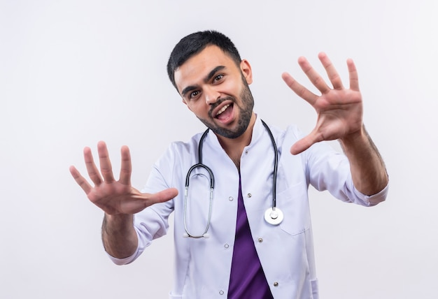 Joyful young male doctor wearing stethoscope medical gown raising hands on isolated white wall