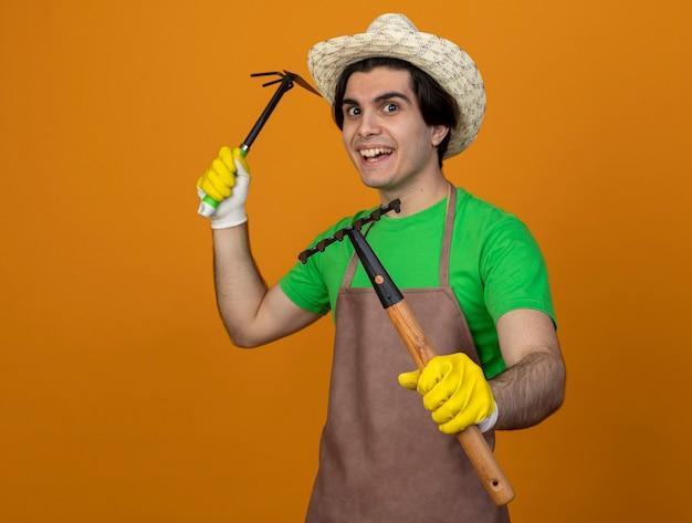 갈퀴와 괭이 갈퀴를 들고 장갑 포즈 싸움에 서있는 원예 모자 서 유니폼을 입고 즐거운 젊은 남성 정원사