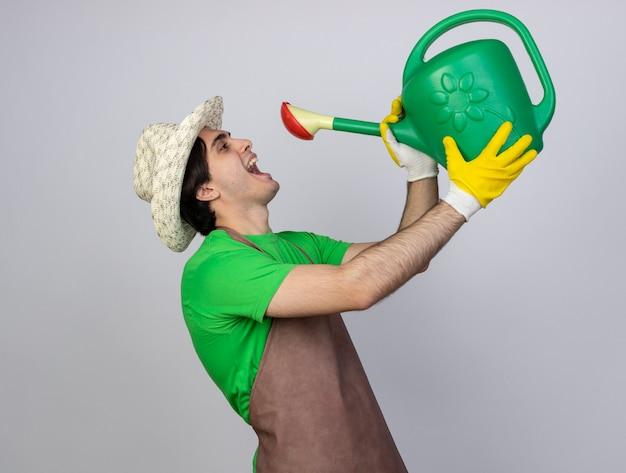 じょうろで自分自身に水をまく園芸帽子を身に着けている制服を着たうれしそうな若い男性の庭師