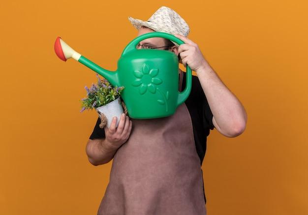 원예 모자와 장갑을 끼고 즐거운 젊은 남성 정원사는 오렌지 벽에 고립 된 화분에 꽃을 들고 물을 수있는 얼굴을 덮었습니다.