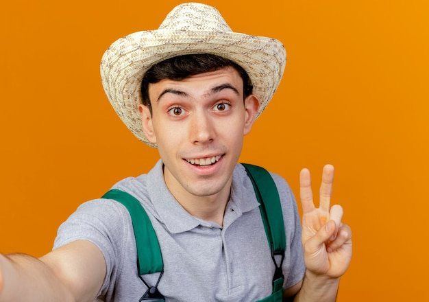 ガーデニング帽子を身に着けているうれしそうな若い男性の庭師は、勝利の手のサインをジェスチャーし、カメラを保持するふりをします