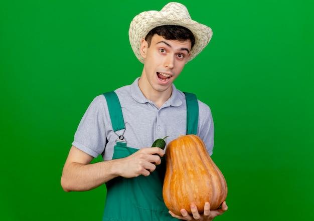 園芸帽子をかぶってうれしそうな若い男性の庭師は、キュウリとカボチャを保持します