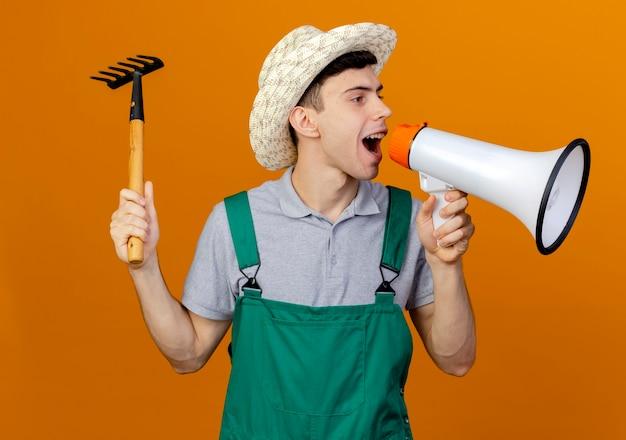 ガーデニング帽子をかぶったうれしそうな若い男性の庭師は熊手を保持し、側面を見てスピーカーに話しかけます