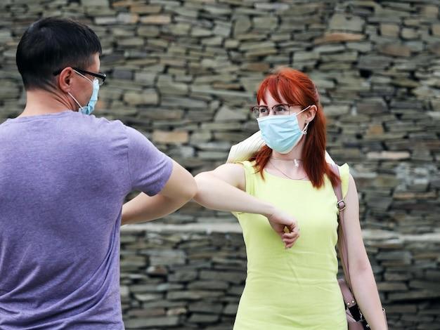握手の代わりに肘に挨拶するうれしそうな若い男と女