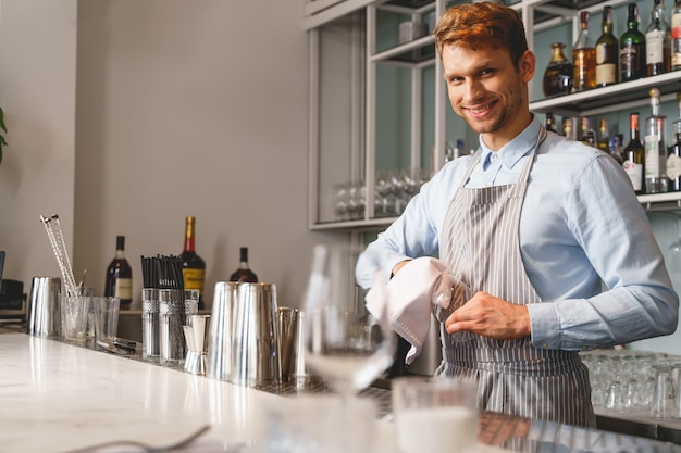 Joyful young man in apron looking and smiling while standing at bar counter and cleaning glass