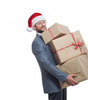 Joyful young man in a christmas hat holding a big pile of gift boxes smiling