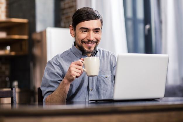 Радостный молодой человек пьет кофе во время использования своего ноутбука