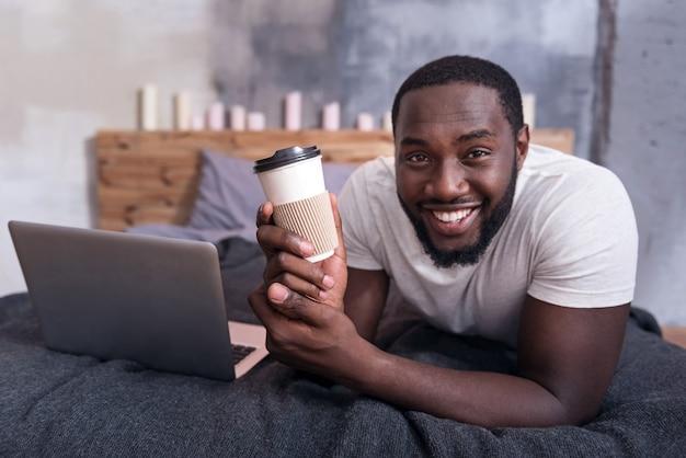 それを飲みながらベッドに横たわっている間コーヒーのカップを保持しているうれしそうな若い男。
