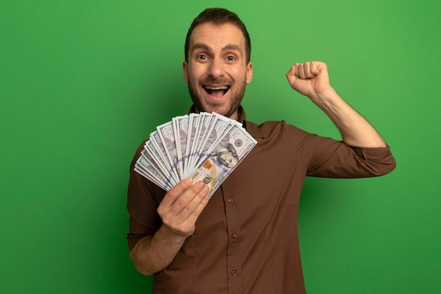 Joyful young man holding money looking at front doing yes gesture isolated on green wall