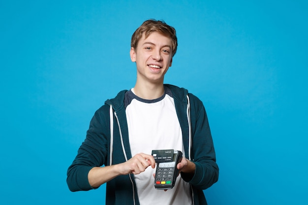 Joyful young man holding wireless modern bank payment terminal to process and acquire credit card payments isolated on blue wall. people sincere emotions, lifestyle concept.