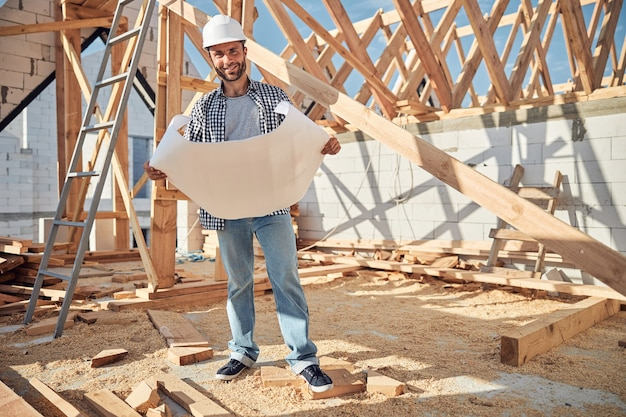 建築計画を保持しているヘルメットのうれしそうな若い男