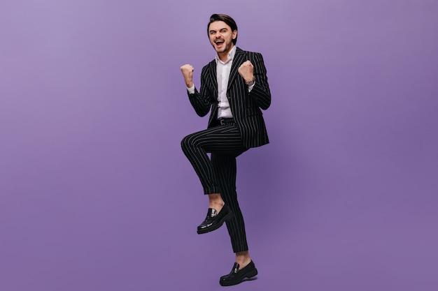 보라색 벽에 긍정적인 감정으로 가득 찬 트렌디한 줄무늬 양복과 검은색 신발을 신은 즐거운 청년