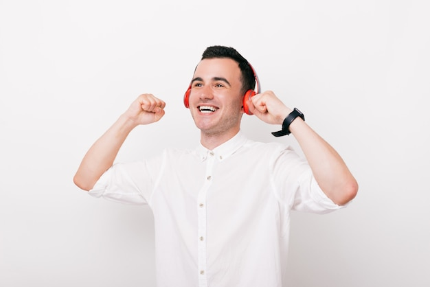 Joyful young man is screaming of happines with headphones on head and listening to the music in studio,on white background.