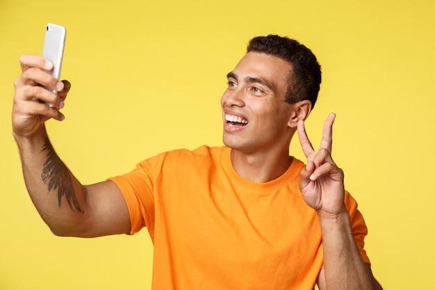 Радостный молодой человек делится положительными эмоциями, принимая селфи, держа смартфон с поднятой рукой