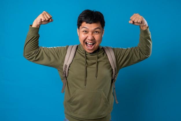Радостный молодой человек студент с рюкзаком позирует на изолированном фоне образование в средней школе