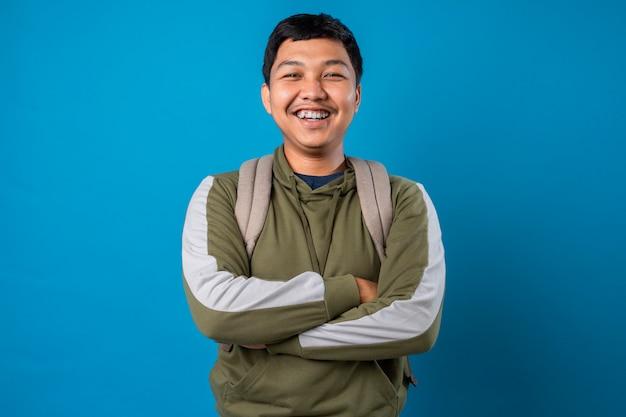Радостный молодой человек студент с рюкзаком позирует на изолированном фоне