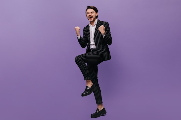 Joyful young man in trendy striped suit and black shoes standing full of positive emotions against violet wall