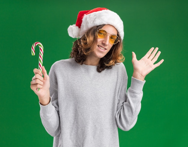 Gioioso giovane uomo che indossa il natale santa hat e occhiali gialli tenendo il bastoncino di zucchero guardando la telecamera sorridendo allegramente con il braccio alzato in piedi su sfondo verde