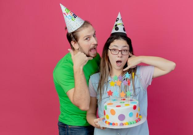 Il giovane allegro che indossa i gesti del cappello del partito mi chiama segno in piedi con la ragazza sorridente che indossa il cappello del partito e che tiene la torta di compleanno che gesticola mi chiama segno isolato sul muro rosa