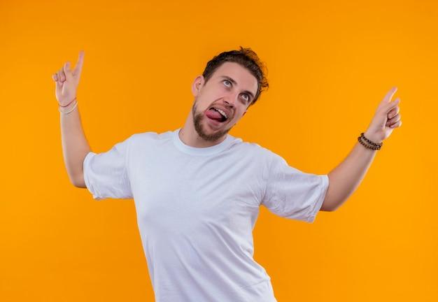 孤立したオレンジ色の壁に舌が上を指す白いtシャツを着てうれしそうな若い男