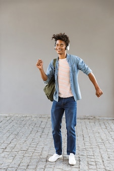 Joyful young man with backpack outdoors