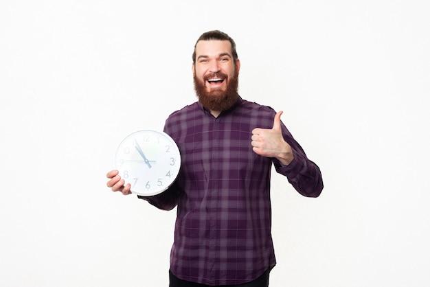 親指を上に表示し、白い壁時計を保持している市松模様のシャツのひげを持つうれしそうな若い男