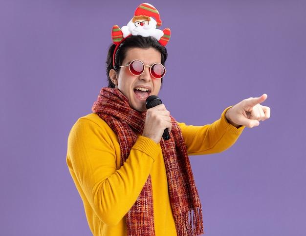 黄色のタートルネックの首の周りに暖かいスカーフと紫色の壁の上に立っているものに人差し指で指してマイクの歌を保持している頭に面白い縁のあるメガネを持つうれしそうな若い男