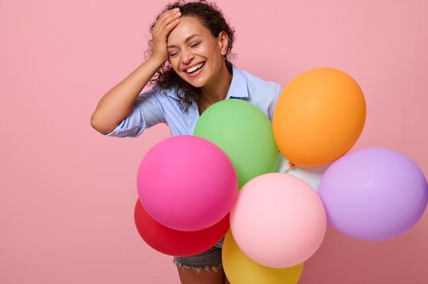 コピースペースとピンク色の背景に分離された、マルチカラーの気球を楽しんで、うれしそうな若い混血の美しい女性が笑います。誕生日パーティー、お祝い、イベントのコンセプト