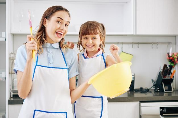 Радостная молодая мать и ее маленькая дочь позируют с силиконовым шпателем и большой пластиковой миской на кухне