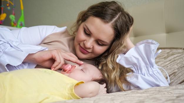 즐거운 젊은 어머니는 여자 아기 근처 큰 침대에 누워