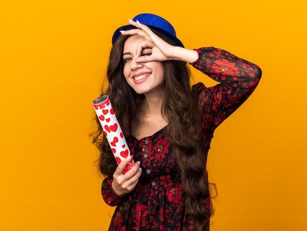 コピースペースでオレンジ色の壁に分離された外観ジェスチャーを行う紙吹雪大砲を保持しているパーティーハットを身に着けているうれしそうな若いパーティーの女の子