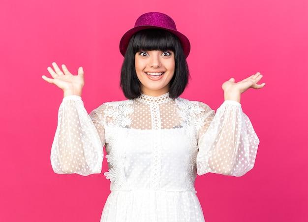 ピンクの壁に隔離された空の手を示すパーティーハットを身に着けているうれしそうな若いパーティーの女の子