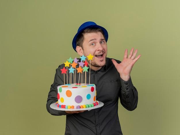 Радостный молодой тусовщик в черной рубашке и синей шляпе держит руку, раскинувшую торт, изолированную на оливково-зеленом