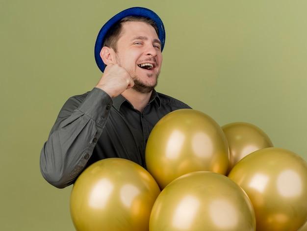 검은 셔츠와 올리브 그린에 고립 된 예 제스처를 보여주는 풍선 뒤에 서있는 파란색 모자를 입고 즐거운 젊은 파티 남자