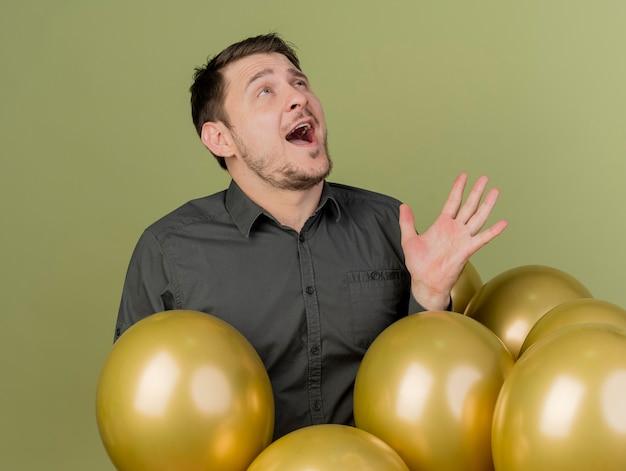 Ragazzo allegro festa giovane che indossa la camicia nera in piedi dietro palloncini isolati su verde oliva